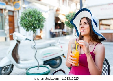 Woman at street terrace in greek village on a hot summer day drinking a orange juice. Summer mediterranean vibe, travel and leisure concept.