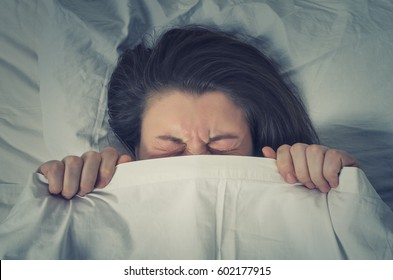 Woman with stressed face expression eyes closed hiding behind sheet in bed.  The concept of avoiding responsibility.