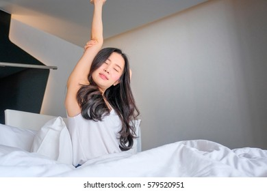 Woman stretch herself out after waking up in the morning