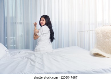 Woman stretching in bed after waking up, back view. Woman sitting near the big white window while stretching .she happy and smile.