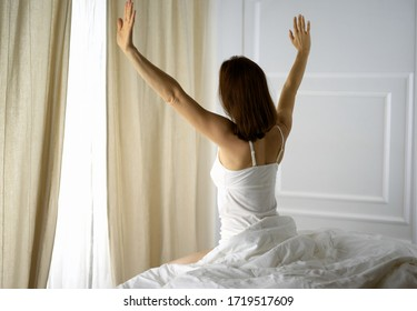 Woman stretching in bed after waking up, back view, entering a day happy and relaxed after good night sleep. Good morning and new day for brunette. Concept of Weekend, holidays