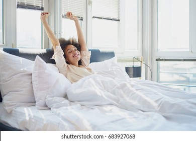 Woman stretching in bed with her arms raised