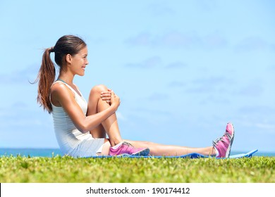 Woman stretching buttocks glute in fitness exercise outside by the ocean sea. Beautiful fit female fitness girl model sitting on grass doing stretch exercising after workout. Mixed race Asian female.