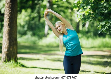 Woman stretching exercise fitness training summer nature time.