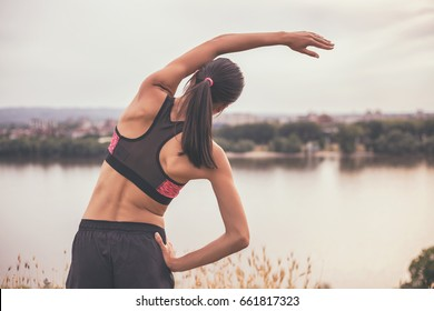 Woman stretching and exercising outdoor.Sporty girl exercising Image is intentionally toned.