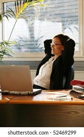 Woman stretching in front of a laptop computer