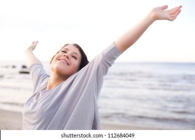 Woman stretching her arms to enjoy the fresh air of the sea