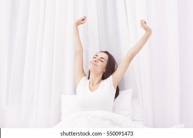 Woman Stretching in Her Bed. A Girl waking up in The Morning. In white bed.