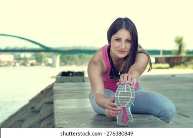 Woman stretching her leg by the river after running...