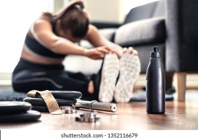 Woman stretching muscles before gym workout and weight training in home living room. Female fitness athlete doing warm up and physical exercise. Warmup before working out. Sportswear and sneakers.