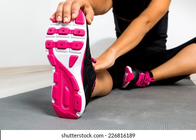 Woman stretching on mat at a gym.