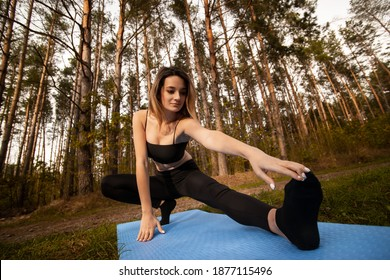Woman stretching on yoga mat in forest. Healthy lifestyle concept. Woman touches her feet. Nature yoga session in beautiful woods, between pine trees. Slim woman wearing black bra, leggins and socks.