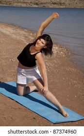 A woman stretching out on a mat on the beach.
