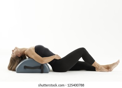 Woman stretching with Pilates machine