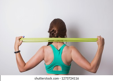 Woman stretching rubber band behind her back. Fitness concept