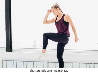 Woman stretching sport at home over window. Studio shot.