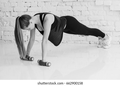 Woman stretching sport at home over brick wall. Studio shot black and white