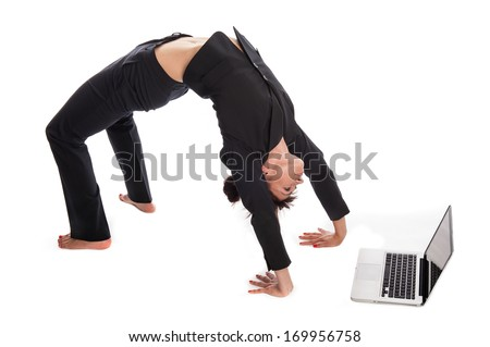 Woman stretching in yoga pose whilst working on a laptop. Isolated on white.