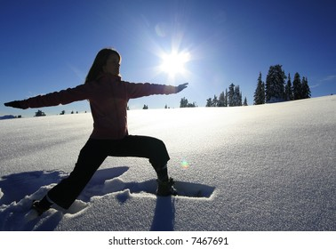 A woman strikes the warrior yoga pose while in a snowy meadow.