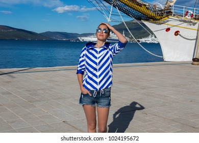 woman in a striped jacket stands at the nose of a ship