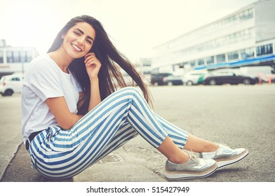 Woman in striped pants and running shoes smiles and tugs at her ear while seated in parking lot