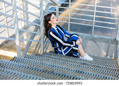 Woman in a striped shirt dress sitting on a metal stairs