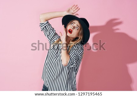 4c2b298064 woman in a striped shirt gesticulates with her hands and a hat on her head  on
