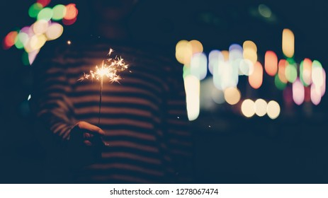 woman with striped shirt holding sparklers in the dark