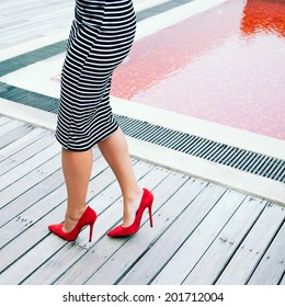 Woman in stripy black and white dress posing near creative red pool in height heeled classic pumps. Fashion image.