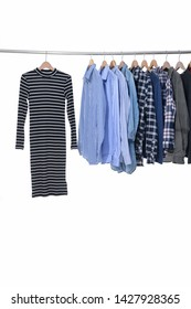 Woman stripy sundress and different blue long sleeve with stripy shirts and jacket, are hanging on metal hangers.