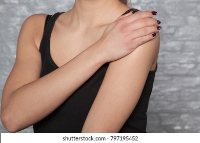 the woman is struggling with rheumatic shoulder pains