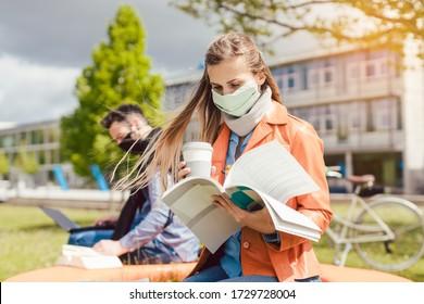 Studentin am College lernt Gesichtsmaske tragen, während sie an ihrem Laptop arbeitet