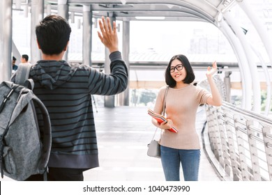 Woman student waving hello with her friend - friendship and togetherness concept