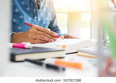 Woman student  writing in diary or reading artistic literature doing homework at home preparing exam , education concept