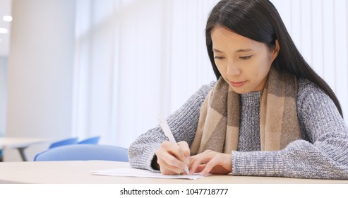Woman student writing on note in library