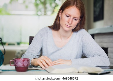 A woman studies the Bible in her living room with a cup of coffee or tea.