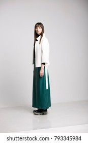 Woman in studio in long skirt and white jacket.