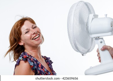 Woman in studio smiles as air from a handheld fan blows her hair