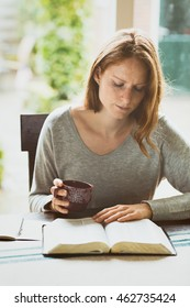 Woman studying the Bible at home with a cup of coffee.