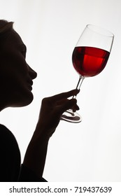 woman studying a glass of red wine