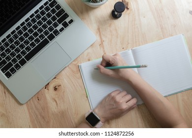 Woman studying with laptop and taking notes on a desktop at cafe. Top view
