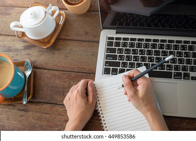 Woman studying with laptop and taking notes on a desktop at cafe