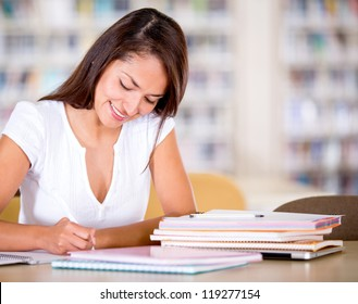 Woman studying at the library looking happy