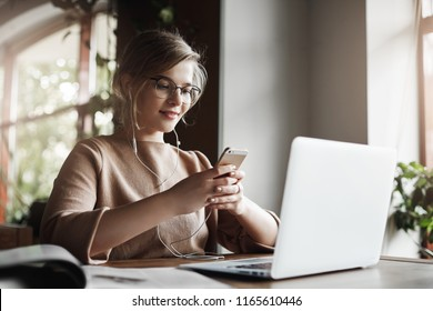 Woman studying and preparing project via laptop, wearing earphones, listening music joyfully, holding smartphone and reading answear on message, being intrigued with future date, taking break