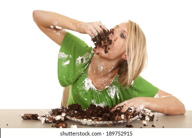 A woman stuffing her face with chocolate cake.  She is covered all over in frosting and cake.