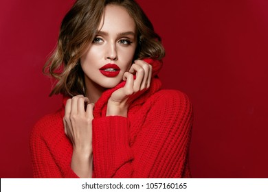 Woman Style. Beautiful Female With Red Lips, Makeup On Face And Hairstyle In Red Pullover Sweater. High Quality