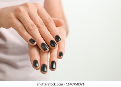 Woman with stylish black manicure on white background, closeup