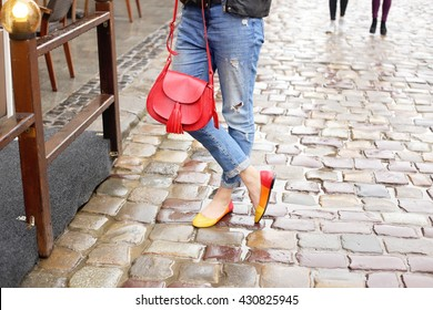 Woman in stylish blue ripped jeans walking down the rainy wet city street with bright red leather handbag and colored ballet flats. Street fashion look. Legs of a young girl on the wet pavement