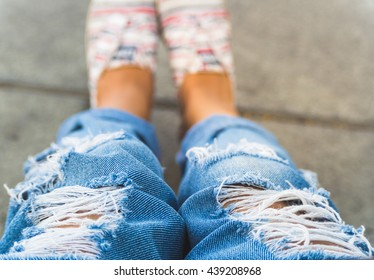 Woman in stylish blue ripped jeans with sneaker. Street fashion look. Legs of a young girl on the pavement. Selective focus.