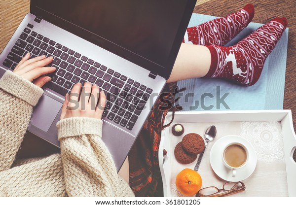 Woman in stylish casual sweater with a laptop on her lap typing on the keyboard and having sweet breakfast with the cup of coffee. The concept of personal productivity and work remotely